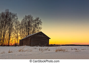 An old barn on the winter fields of the Northern Finland. The midwinter sun sets early over the snowy fields.