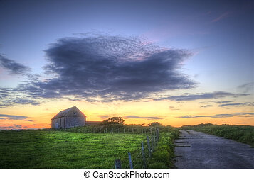 Sunset landscape image of old barn in countryside fields