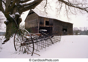 Old barn in the snow - An old barn with farm equipment in...