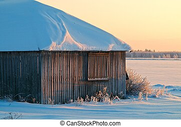 Old barn in winter sunset.