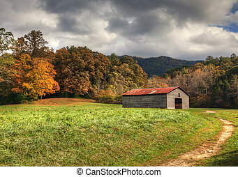 Old barn with beautiful fall colors and cloudy skies.