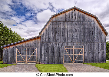 Old barn on a farm, cloudy sky in background.