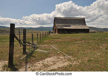 Old barn in a field with clouds
