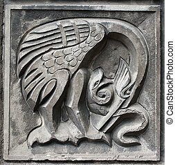 old bas-relief of fairytale heron and snake - old bas-relief...