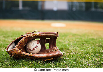 Old Baseball and Glove on Field - Old baseball and glove on...