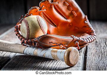 Old baseball ball and golden glove