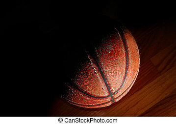 old basketball closeup in dramatic light on the gym floor