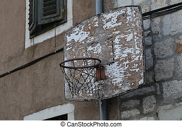 Old basketball ring is attached to the wall of the house