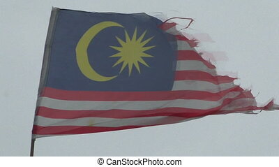 Old battered Malaysia flag in the breeze develops. Real...
