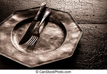 Old battered rustic pewter plate with cutlery