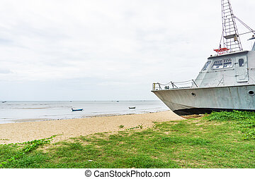 Battle metal ship on sand beach