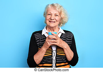 old beautiful smiling woman holding a cup of tea and looking at the camera