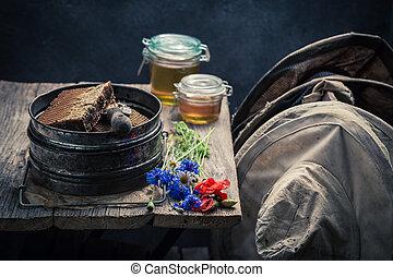 Old beekeeper tools in workshop with honey