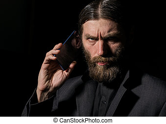 Old believer senior priest with a smartphone, bearded old man is calling on a dark background