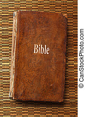 Old Bible book on the straw weaving background