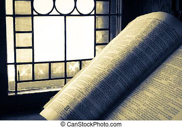 Old Bible lit by stained glass