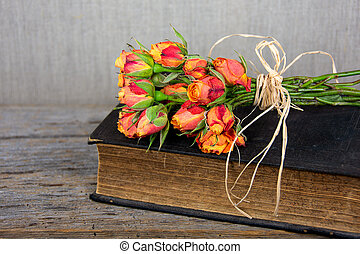 old Bible with orange rose bouquet