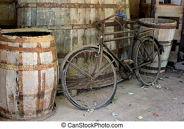 Interesting photo of an old bicycle leaning against some wine barrels at an Italian winery in Italy.