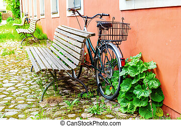 old bicycle leaning against a house wall
