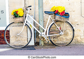 Old bicycle leaning against a shop wall