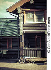 Old bicycle leaning against house wall
