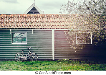 Old bicycle leaning against wooden barn