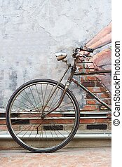 Old bicycle leaning on the wall