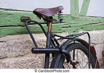Old bicycle locked at a wall