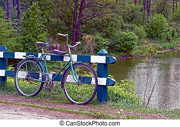 Old bicycle near the fence on the shore of the reservoir