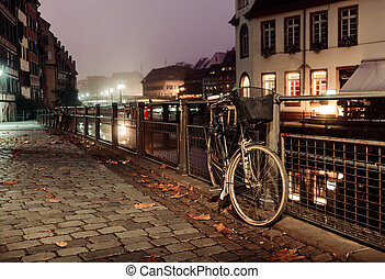 Old bicycle on city cobblestones fastened to the fence lit by the lights of the night city