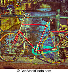 Old bicycle on the canal bridge in Amsterdam