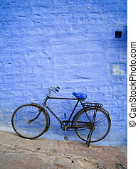 Old bike leans up against a bright blue brick wall