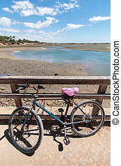 Old bike parked to a view of the Ria Formosa marshlands located in the Algarve, Portugal.
