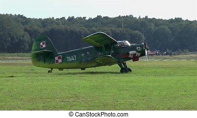 Antonov An-2 biplane on a grass runway.