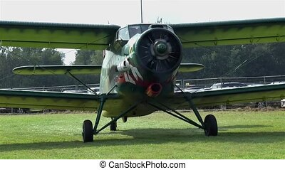 Old biplane on a grass runway.