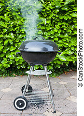 Old black barbecue being used