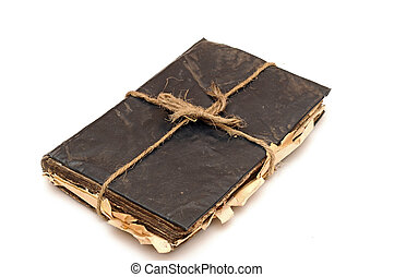 Old black book tied up by a rope isolated on a white background