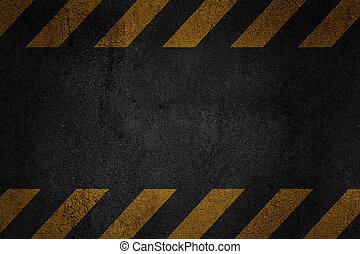 Old black grungy asfalt surface with yellow warning stripes...