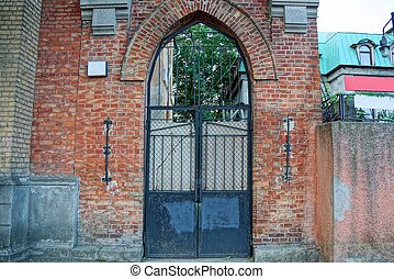 old black iron gate on a brown brick building wall