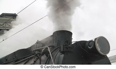 old black locomotive. steam smoking in real time.