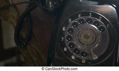 Old black rotary phone dolly shot in 4k with a ceiling fan reflection in the corner of the telephone