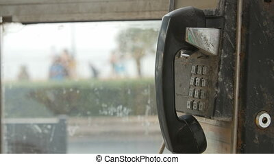 Old black rusty phone in phone booth coin. A woman's hand...