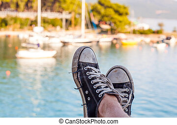 Old black sneakers on the background of the sea with yachts