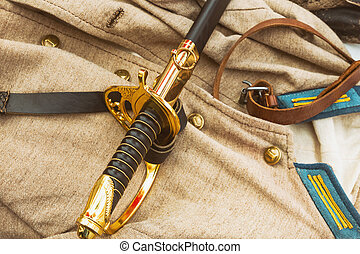 old black sword with a gold handle on the background of military uniforms closeup design military
