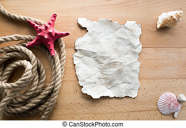 Old blank piece of paper lying on desk with ropes and seashells