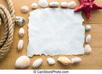 blank piece of paper with seashells, rope and starfish