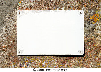 Old blank sign on a stone wall ready for text.