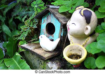 Old blue bird house with ceramic bird and boy