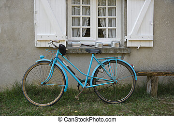 Old blue french bicycle in front of window