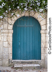 Old blue green door in a stone wall with flowers above